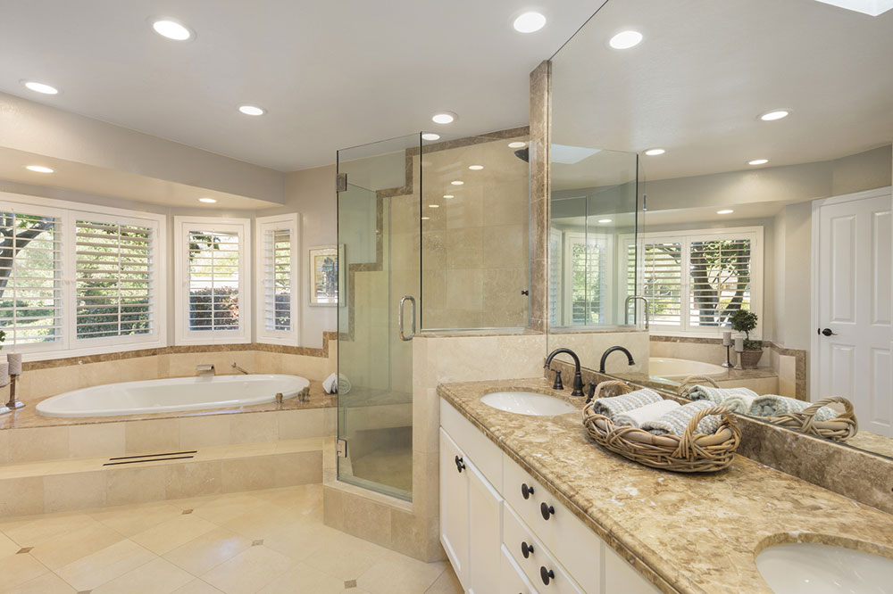Luxury bathroom interior in marble with glass shower and round double sink.