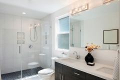 Modern bathroom interior with glass door shower and white cabinet with mirror.