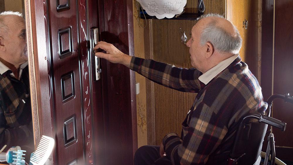 Man in a wheelchair checking his house locks