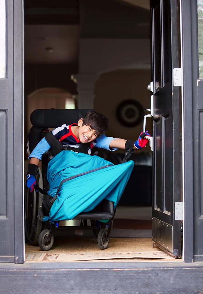 Disabled boy in wheelchair opening front door